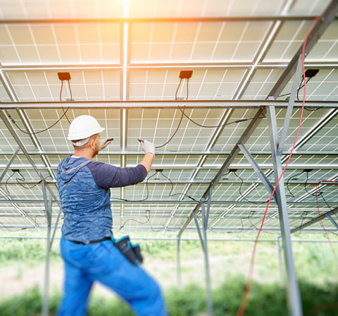 man working underneath solar panel